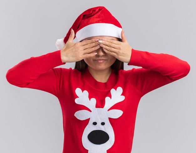 Zadowolona młoda azjatycka dziewczyna ubrana w świąteczny kapelusz ze swetrem zakryte oczy rękami na białym tle