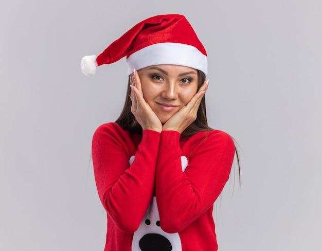 Zadowolona młoda azjatycka dziewczyna ubrana w świąteczny kapelusz ze swetrem zakryte policzki rękami na białym tle