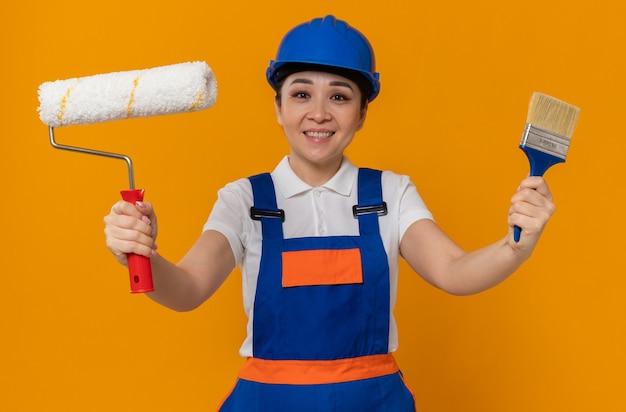 Zadowolona młoda azjatycka kobieta budowlana w niebieskim kasku ochronnym trzymająca wałek do malowania i pędzel
