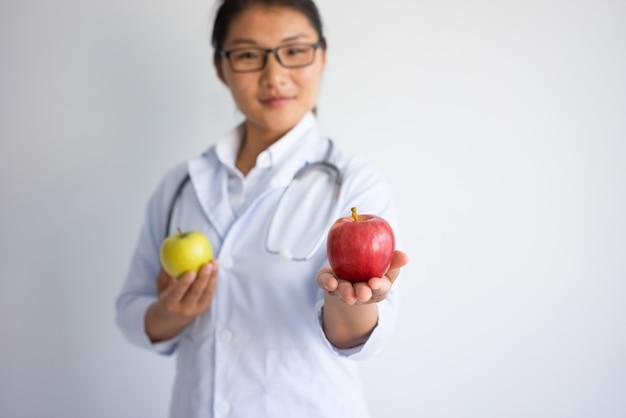 Zadowolona młoda azjatycka kobiety lekarki ofiary czerwony jabłko.