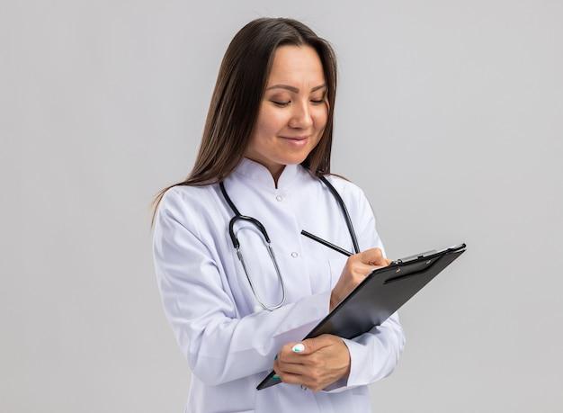 Zadowolona młoda azjatycka lekarka nosząca szatę medyczną i stetoskop trzymający schowek i pióro piszące receptę patrząc na schowek na białym tle na białej ścianie