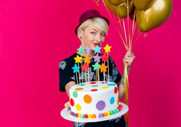 Zadowolona młoda blond impreza w kapeluszu imprezowym, patrząc na kamerę trzymającą balony i wyciągającą tort urodzinowy z gwiazdami w kierunku kamery na białym tle na szkarłatnym tle z przestrzenią do kopiowania