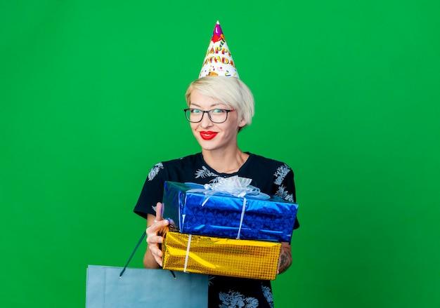 Zadowolona młoda blond imprezowiczka w okularach i czapce urodzinowej trzymająca papierową torbę i pudełka na prezenty, patrząc na przód odizolowany na zielonej ścianie z miejscem na kopię