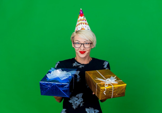 Zadowolona młoda blond kobieta w okularach i czapce urodzinowej, trzymając pudełka z prezentami, patrząc z przodu na białym tle na zielonej ścianie z miejsca na kopię