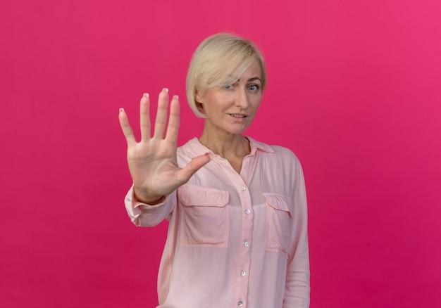 Zadowolona młoda blond słowiańska kobieta, patrząc na kamery i pokazując pięć ręką na białym tle na różowym tle z miejsca na kopię
