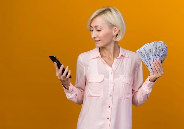 Zadowolona młoda blond słowiańska kobieta trzyma gotówkę i patrząc na telefon w dłoni