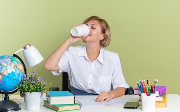 Zadowolona młoda blond studentka siedząca przy biurku z szkolnymi narzędziami trzymająca rękę na biurku pijąca kawę z plastikowego kubka do kawy