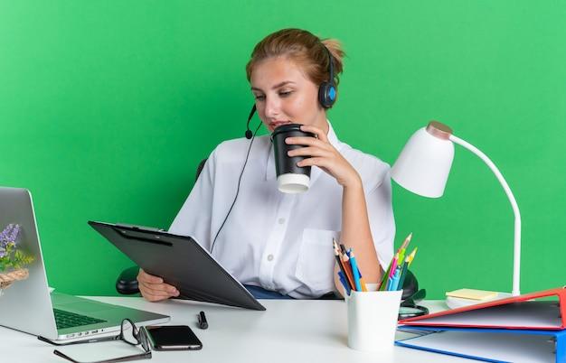Zadowolona młoda blondynka call center dziewczyna nosi zestaw słuchawkowy, siedząc przy biurku z narzędziami do pracy, trzymając plastikową filiżankę kawy i schowek, patrząc na schowek na białym tle na zielonej ścianie