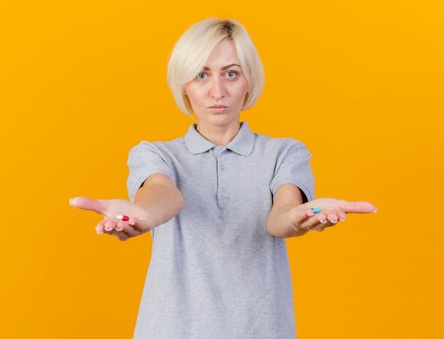 Zadowolona młoda blondynka chora kobieta trzyma pigułki medyczne na białym tle na pomarańczowej ścianie