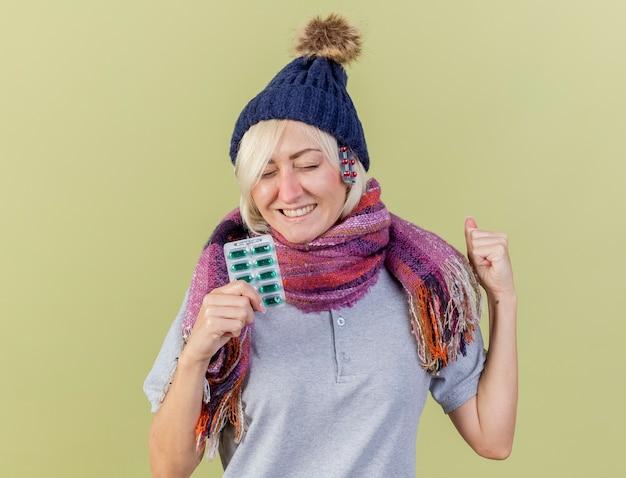 Zadowolona młoda blondynka chora słowiańska kobieta w czapce zimowej