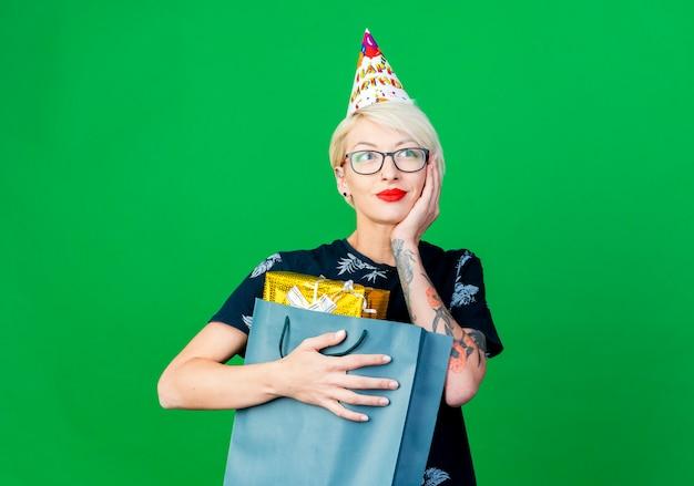 Zadowolona młoda blondynka imprezowa w okularach i czapce urodzinowej trzymająca papierową torbę z pudełkami na prezenty, trzymając dłoń na twarzy patrząc w bok, śniąc na białym tle na zielonym tle z miejscem na kopię