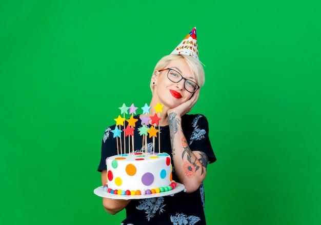 Zadowolona młoda blondynka imprezowiczka w okularach i czapce urodzinowej trzymająca tort urodzinowy z gwiazdami, trzymając rękę na twarzy, patrząc na kamerę odizolowaną na zielonym tle z przestrzenią do kopiowania
