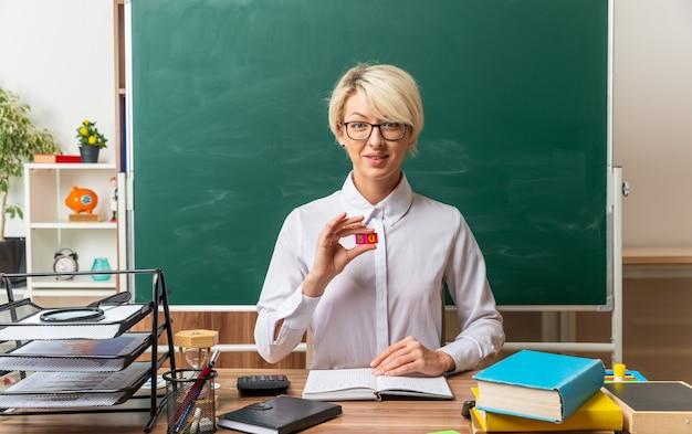 Zadowolona młoda blondynka nauczycielka w okularach, siedząca przy biurku z szkolnymi narzędziami w klasie, pokazująca małe kwadratowe cyfry pięć i zero