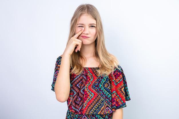 Zadowolona młoda blondynka słowiańska kładzie palec na nosie i