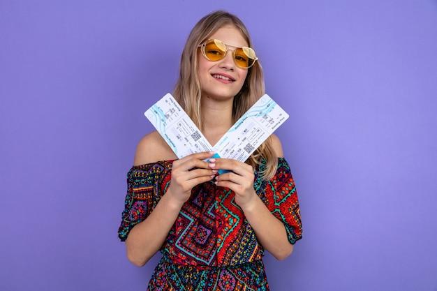 Zadowolona młoda blondynka słowiańska w okularach przeciwsłonecznych trzymająca bilety lotnicze