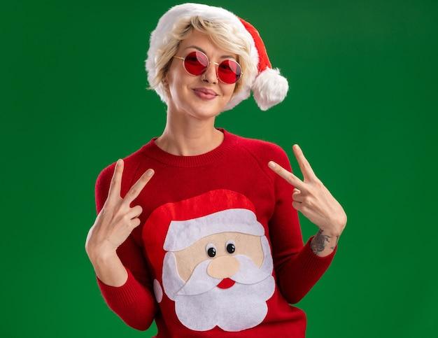 Zadowolona młoda blondynka ubrana w świąteczny kapelusz i świąteczny sweter świętego mikołaja w okularach, patrząc na kamery, robi znak pokoju na białym tle na zielonym tle
