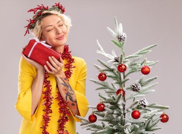 Zadowolona młoda blondynka ubrana w świąteczny wieniec i girlandę ze świecidełek na szyi stojącą w pobliżu ozdobionej choinki trzymającej pakiet prezentów z zamkniętymi oczami na białym tle na białej ścianie