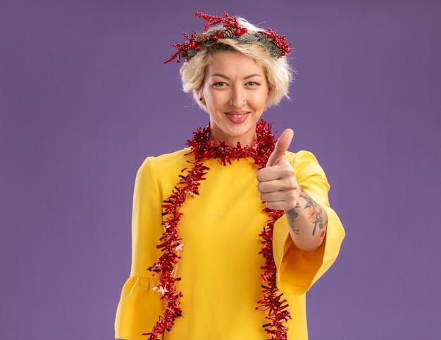 Zadowolona młoda blondynka ubrana w świąteczny wieniec na głowę i girlandę z blichtru wokół szyi, patrząc pokazując kciuk w górę odizolowaną na fioletowej ścianie z kopią miejsca