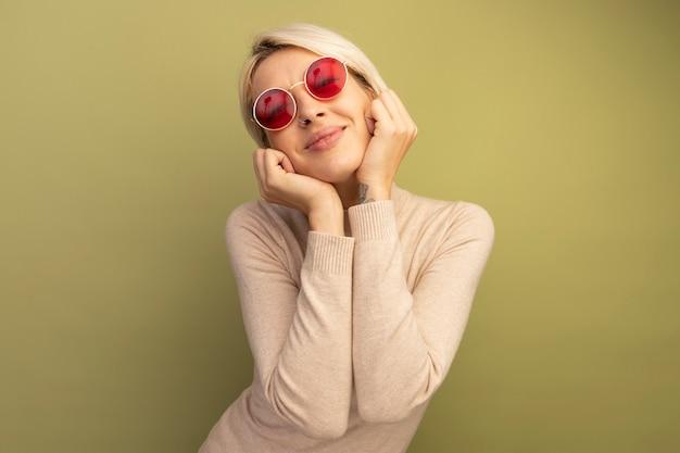 Zadowolona młoda blondynka w okularach przeciwsłonecznych, kładąc ręce na twarzy