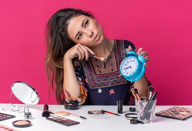 Zadowolona młoda brunetka dziewczyna siedzi przy stole z narzędziami do makijażu, trzymając budzik i pędzel do makijażu