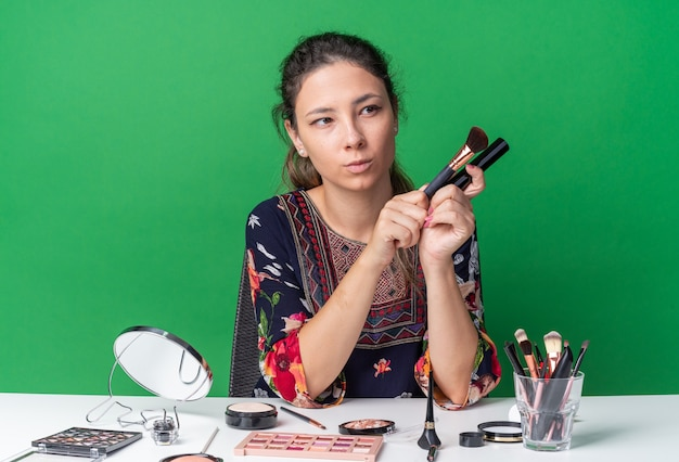 Zadowolona młoda brunetka dziewczyna siedzi przy stole z narzędziami do makijażu, trzymając pędzel do makijażu i tusz do rzęs, patrząc na bok