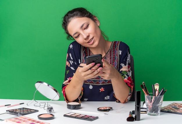 Zadowolona młoda brunetka dziewczyna siedzi przy stole z narzędziami do makijażu, trzymając telefon i patrząc na telefon na zielonej ścianie z miejscem na kopię