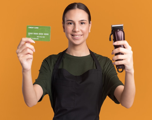 Zadowolona młoda brunetka fryzjerka w mundurze trzymająca maszynkę do strzyżenia włosów i kartę kredytową