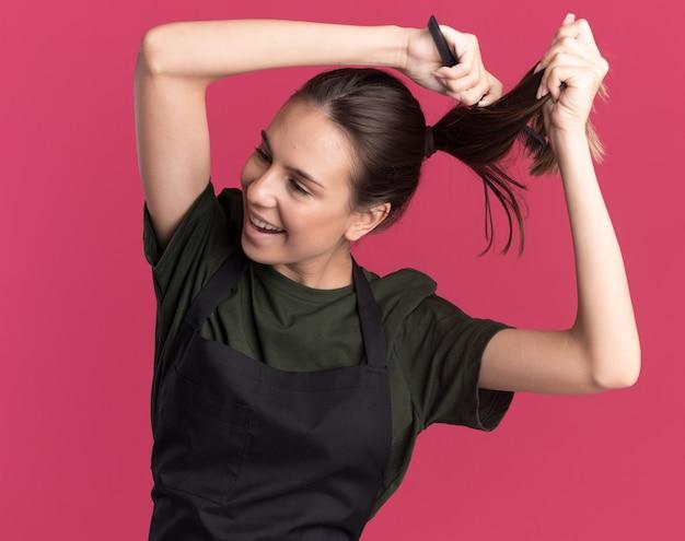 Zadowolona młoda brunetka fryzjerka w mundurze udaje, że ścina włosy nożyczkami do przerzedzania włosów, patrząc na bok na różowej ścianie z kopią przestrzeni
