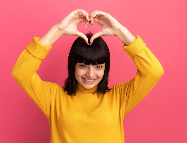 Zadowolona młoda brunetka kaukaska dziewczyna gestykuluje znak serca nad głową