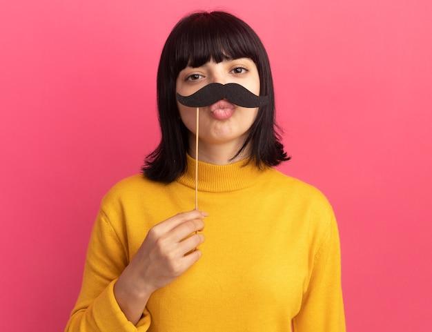 Zadowolona młoda brunetka kaukaska dziewczyna trzyma sztuczne wąsy na patyku