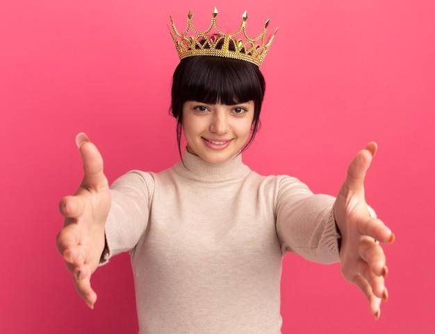 Zadowolona młoda brunetka kaukaska dziewczyna z koroną wyciąga ręce odizolowaną na różowej ścianie z miejscem na kopię