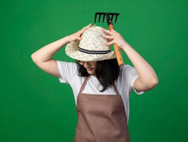 Zadowolona młoda brunetka ogrodniczka w okularach optycznych i mundurze, nosząca i wkładająca ręce na kapelusz ogrodniczy, trzymając prowizję na białym tle na zielonej ścianie