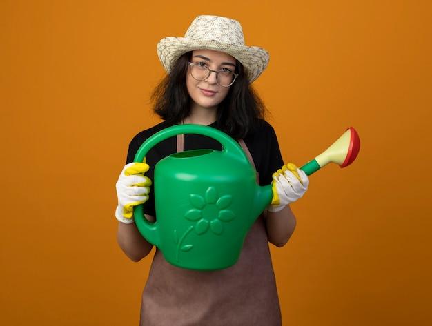 Zadowolona młoda brunetka ogrodniczka w okularach optycznych i mundurze w kapeluszu ogrodniczym i rękawiczkach trzyma konewkę na pomarańczowej ścianie
