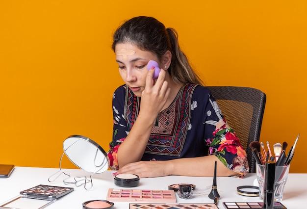 Zadowolona młoda brunetka siedzi przy stole z narzędziami do makijażu, nakładająca podkład z gąbką i patrząca w lustro izolowane na pomarańczowej ścianie z miejscem na kopię