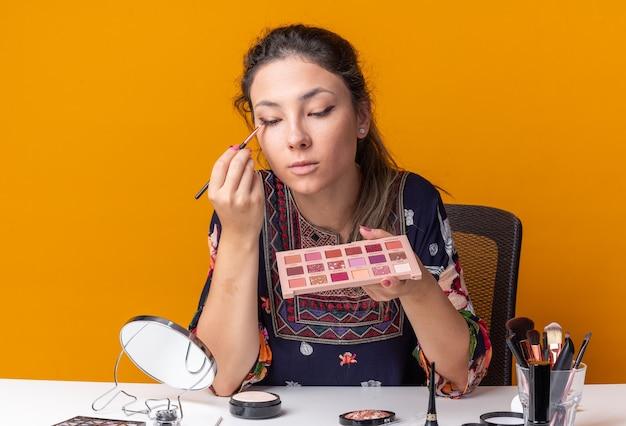 Zadowolona młoda brunetka siedzi przy stole z narzędziami do makijażu, trzymając paletę cieni do powiek i nakładając cień do powiek za pomocą pędzla do makijażu, patrząc w lustro