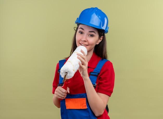 Zadowolona młoda budowniczy dziewczyna w niebieskim kasku ochronnym trzyma wałek do malowania jak mikrofon obiema rękami na odosobnionym zielonym tle