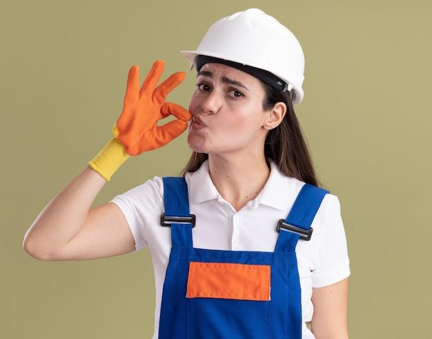 Zadowolona młoda budowniczy kobieta w mundurze i rękawiczkach pokazująca pyszny gest na tle oliwkowej ściany