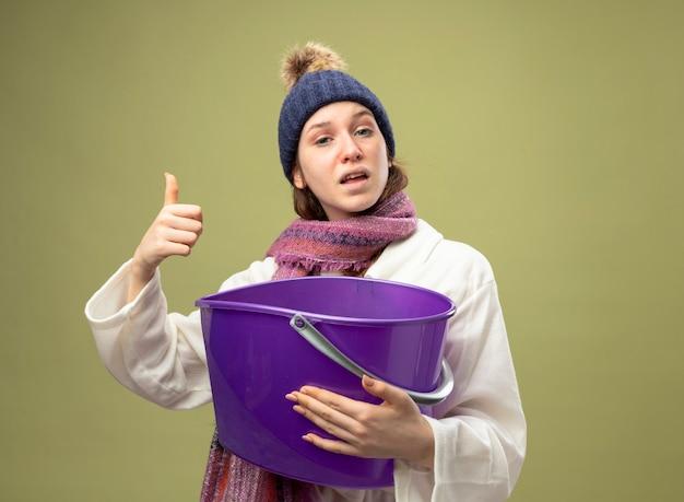 Zadowolona młoda chora dziewczyna ubrana w białą szatę i czapkę zimową z szalikiem trzymająca plastikowe wiaderko pokazująca kciuk do góry na białym tle na oliwkowej zieleni