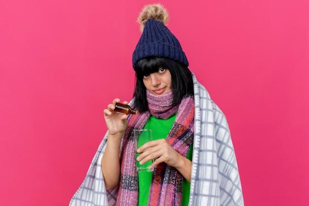 Zadowolona młoda chora dziewczynka kaukaska w czapce zimowej i szaliku owinięta w kratę, wlewająca lekarstwo do szklanki do szklanki wody, patrząc na kamerę odizolowaną na szkarłatnym tle z miejscem na kopię