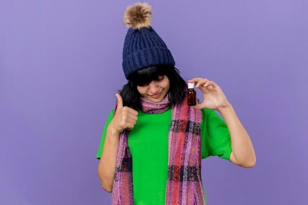 Zadowolona młoda chora dziewczynka kaukaska w czapce zimowej i szaliku, trzymając i patrząc na lek w szkle, pokazując kciuk do góry na białym tle na fioletowym tle z miejscem na kopię