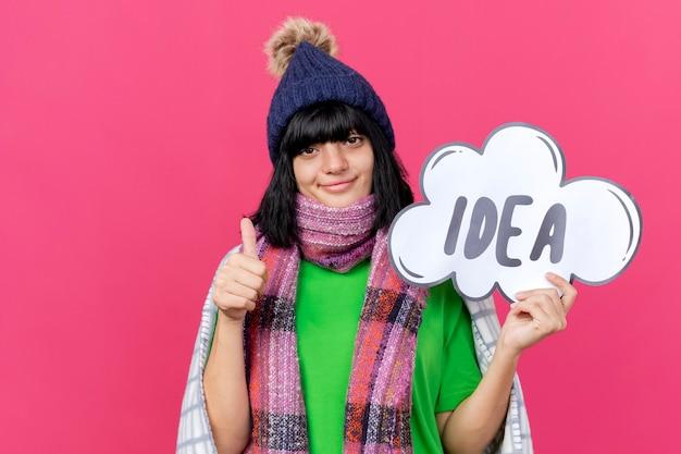Zadowolona młoda chora kaukaska dziewczyna w czapce zimowej i szaliku owinięta w kratę, trzymając bańkę pomysłu patrząc na kamerę, pokazując kciuk w górę na białym tle na szkarłatnym tle z miejscem na kopię