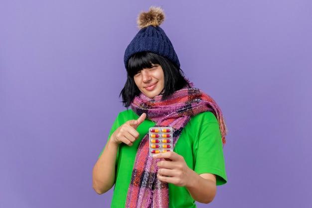 Zadowolona młoda chora kaukaska dziewczyna w czapce zimowej i szaliku trzymająca paczkę kapsułek patrząc i wskazując na aparat odizolowany na fioletowym tle z miejsca na kopię