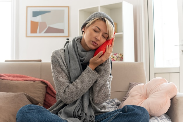 Zadowolona młoda chora słowiańska kobieta z szalikiem na szyi w czapce zimowej trzymająca głowę na termoforze siedząca na kanapie w salonie