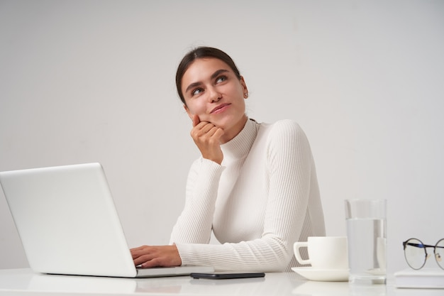 Zadowolona młoda ciemnowłosa ładna kobieta z naturalnym makijażem, pochylająca głowę z uniesioną ręką i patrząca pozytywnie w górę z radosnym uśmiechem, siedząca na białej ścianie