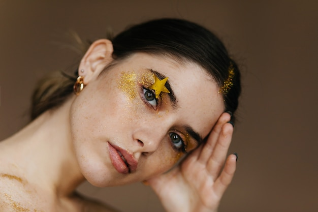 Zadowolona młoda dama z efektownym makijażem. pozytywna brunetka dziewczyna dotyka jej czoła.