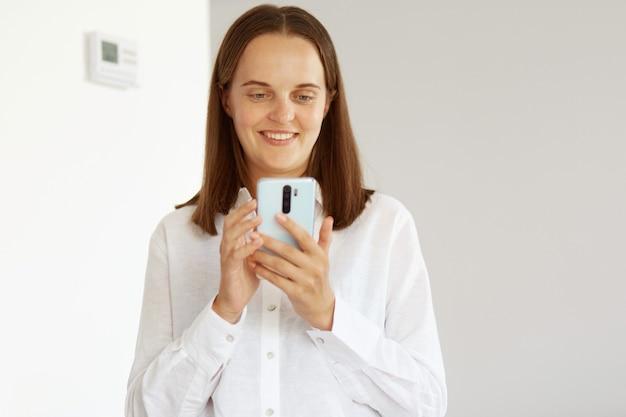 Zadowolona młoda dorosła kobieta nosi białą koszulę w stylu casual, pozuje w jasnym pokoju w domu, trzymając telefon komórkowy, patrząc na ekran gadżetu, pisząc wiadomość lub sprawdzając sieci społecznościowe.