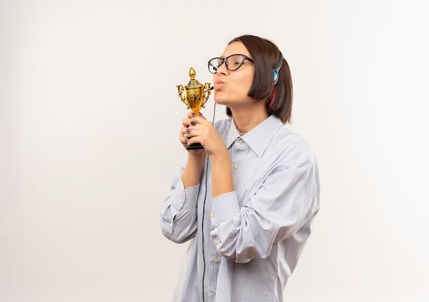 Zadowolona młoda dziewczyna call center w okularach i zestaw słuchawkowy całuje puchar zwycięzcy z zamkniętymi oczami na białym tle na białym tle z miejsca na kopię