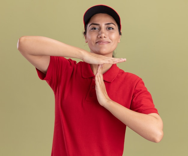 Zadowolona młoda dziewczyna dostawy ubrana w mundur z czapką pokazującą gest przekroczenia limitu czasu na białym tle na oliwkowej ścianie