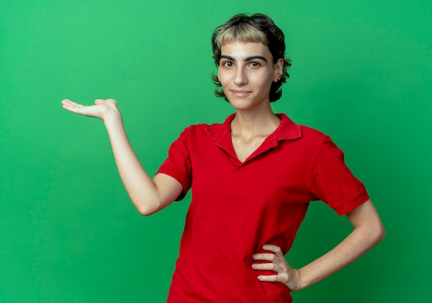 Zadowolona młoda dziewczyna kaukaska z fryzurą pixie kładąca rękę na talii i pokazująca pustą dłoń na białym tle na zielonym tle