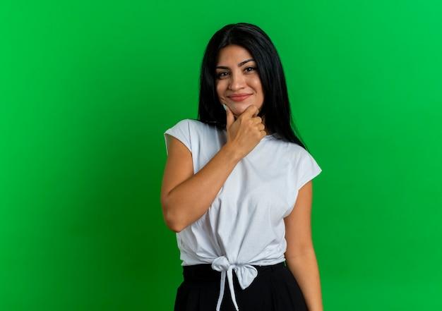 Zadowolona młoda dziewczyna kaukaski kładzie rękę na podbródku, patrząc